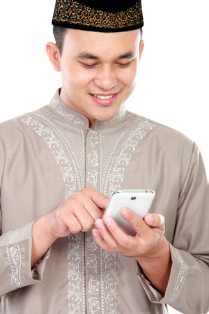 spiritually: portrait of young muslim man typing on his smartphone with white background Stock Photo