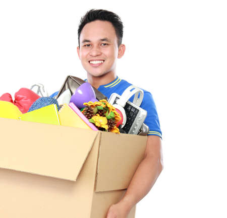 man carrying box: portrait of happy young man carrying box full of stuff on white background