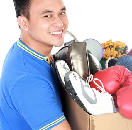 man carrying box: close up portrait of handsome young man carrying box full of stuff