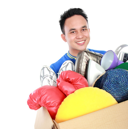 portrait of box full of goodies carried by handsome young man on white background photo