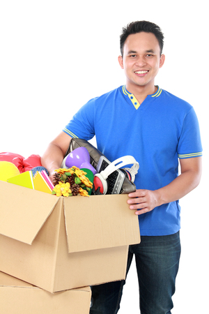 portrait of young man holding a box full of stuff on white background photo
