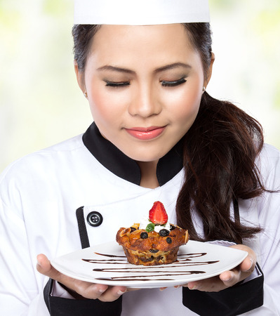 portrait of beauty woman Chef hold a plate and presenting dessert photo