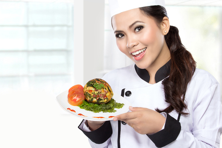 portrait of beauty woman Chef hold a plate and presenting dessert