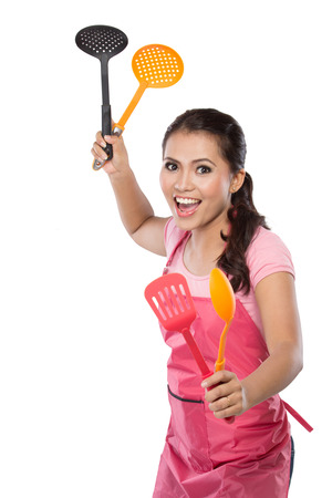 exasperation: portrait of beauty young wife in action and hold spatula Stock Photo