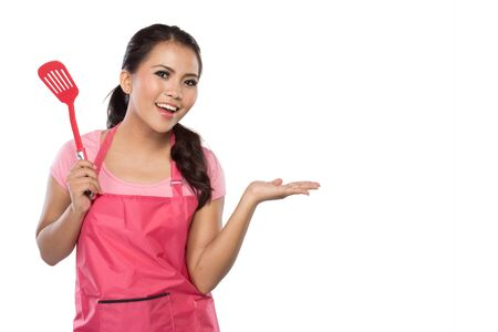 kitchen tool: beauty young wife hold a spatula and presenting a blank area