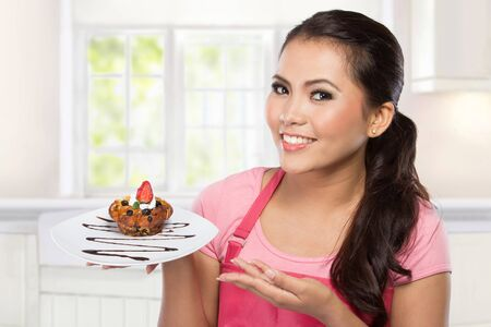 asian cook: pretty young wife hold a plate of dessert and presenting