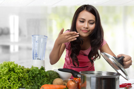 tasting: Young Woman Cooking in the kitchen. Healthy Food Diet. Cooking At Home. Prepare Food