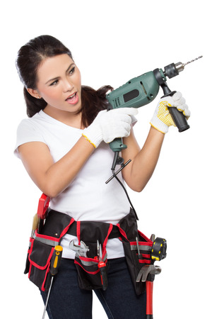 savety: female wearing working clothes with toolbelt using electric drill