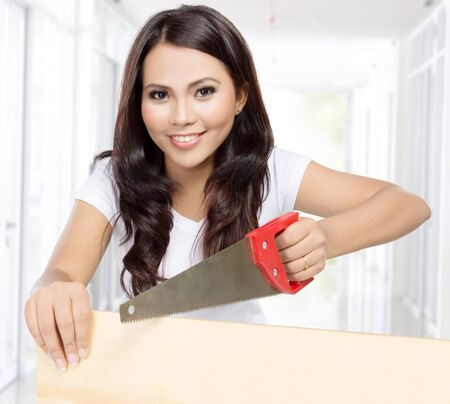 savety: portrait of pretty housewife doing some contruction work with saw