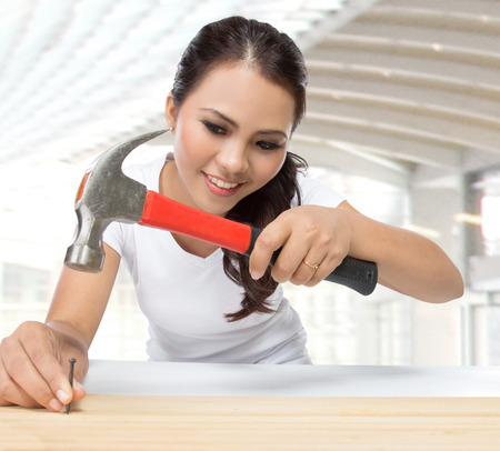 beauty young woman construction worker put nail on the wood using hammer