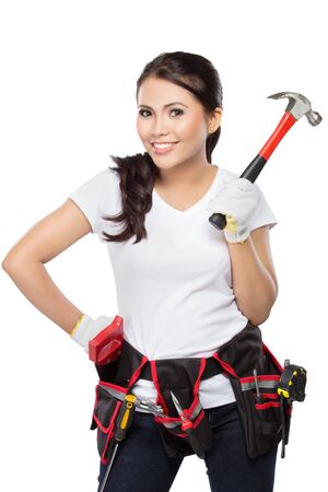 tools belt: Female construction worker wearing a  tool belt full of a variety of useful tools hold a  hammer Stock Photo
