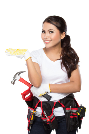 resent: Female construction worker wearing a  tool belt full of a variety of useful tools and presenting