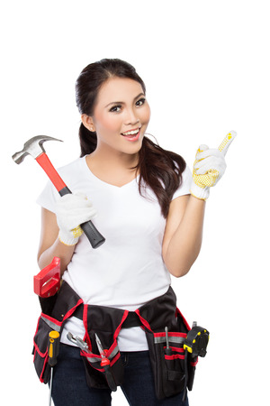 female construction worker: Female construction worker wearing a  tool belt full of a variety of useful tools and pointing up Stock Photo