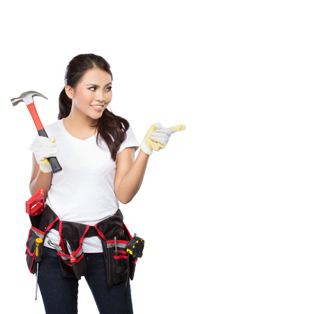 tools belt: Female construction worker wearing a  tool belt full of a variety of useful tools and pointing up Stock Photo