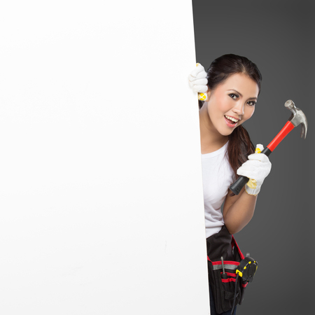 resent: portrait of Female Construction Worker With Toolbelt hold a white banner Stock Photo