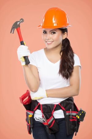 savety: A woman wearing a  tool belt full of a variety of useful tools hold a hammer