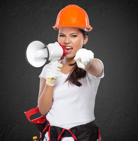 savety: portrait of Female Construction Worker With Toolbelt south on megaphone