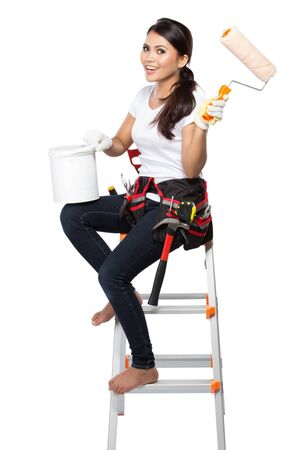 step ladder: Painting worker woman standing on step ladder painting the walls