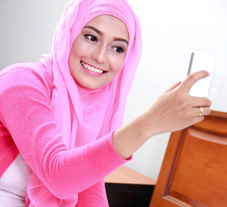 portrait of young woman wearing pink hijab taking selfie photo with mobilephone Stock Photo