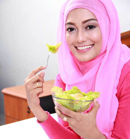 hijab: portrait of cheerful young muslim woman eating healthy breakfast on bed