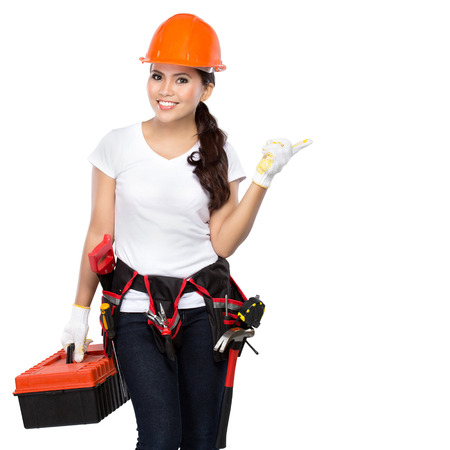 Female construction worker wearing a  tool belt full of a variety of useful tools and pointing up Archivio Fotografico