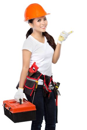 savety: female wearing working clothes with toolbelt holding toolbox and pointing up