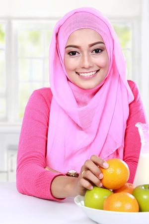 肖像画の陽気な若いイスラム教徒の女性はフルーツ朝食を食べた 写真素材 - 37682120
