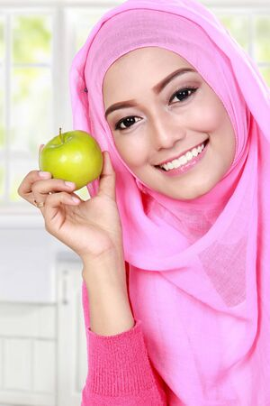 cheerful young muslim woman holding an apple photo