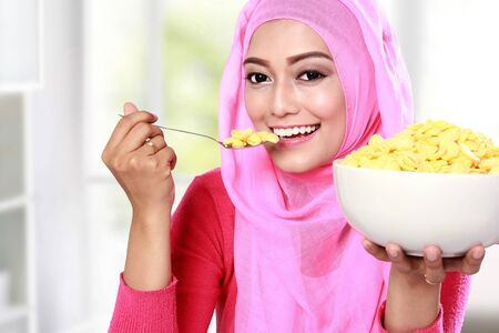 portrait of young muslim woman eating cereal for breakfast