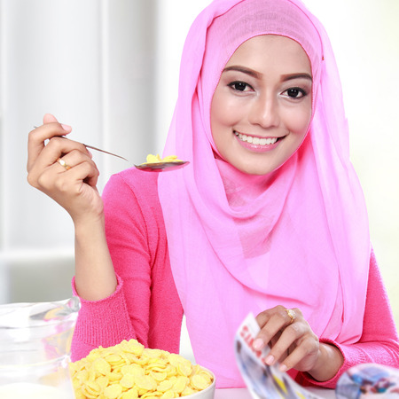 adult magazine: close up portrait of young muslim woman eating a cereal while reading a magazine Stock Photo