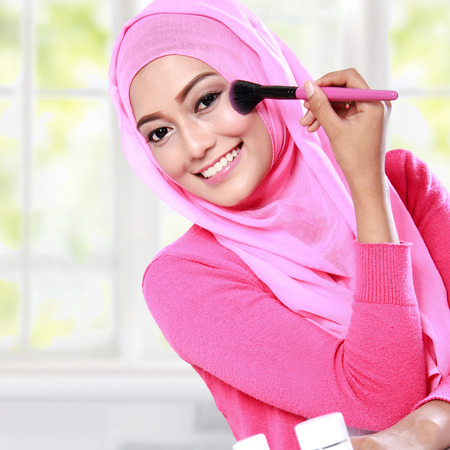 muslimah: portrait of cheerful young woman wearing hijab applying blush on
