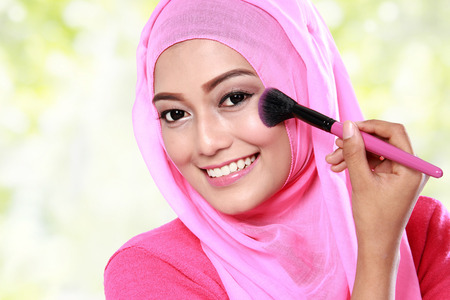 close up portrait of cheerful young muslim woman applying blush on Stock Photo