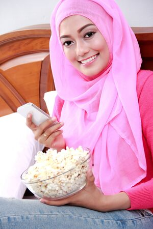 bowl of popcorn: portrait of young woman wearing hijab holding a mobilephone and a bowl of popcorn on bed Stock Photo