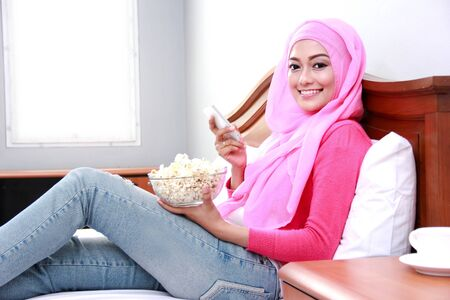 popcorn bowls: portrait of young muslim woman holding mobilephone and a bowl of popcorn on bed Stock Photo