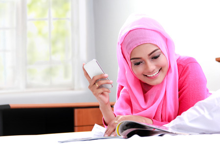 girl bedroom: portrait of young muslim woman reading a magazine on bed