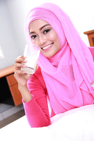 girl bedroom: portrait of beautiful young muslim woman drinking a glass of milk for breakfast Stock Photo