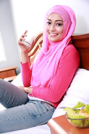 glass bed: portrait of beautiful young muslim woman holding a glass of milk for breakfast on bed Stock Photo