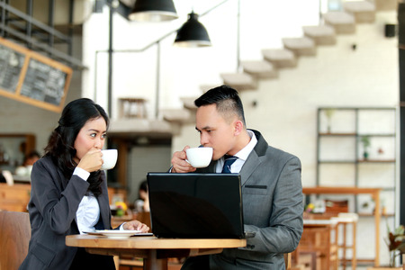 taking a break: portrait of businessman and businesswoman taking a coffee break while discussing new project Stock Photo