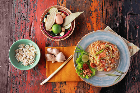 noodle bowl: portrait of seafood pad thai with some ingredients