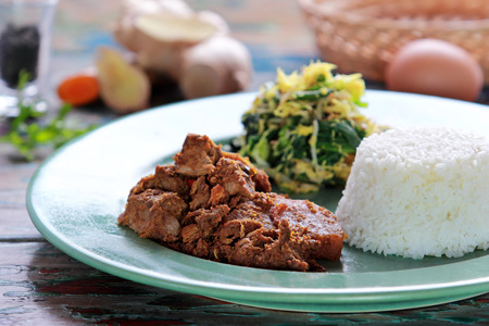 portrait of beef rendang served with  urap and rice Stock Photo
