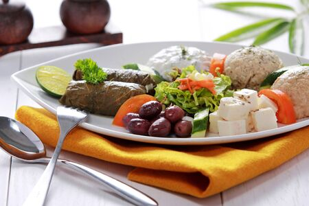 Greek vegetarian food mix pikilia with hummus, tzatziki, feta cheese, dolmades and olives served in dish