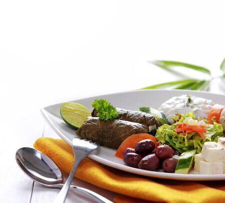 Greek vegetarian food mix pikilia with hummus, tzatziki, feta cheese, dolmades and olives on white background photo