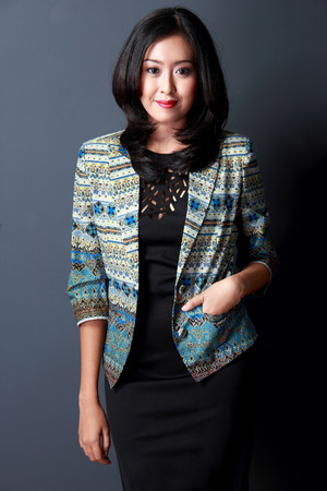blazer: portrait of fashionable young woman wearing black dress and blue tribal coat