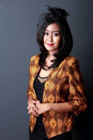 batik: Portrait de sourire belle femme portant robe noire et manteau de batik Banque d'images