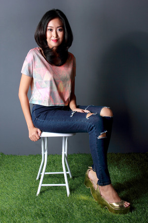 fashion shoot: fashion shoot of beautiful woman sitting on white chair wearing crop tees, denim trousers and gold wedges