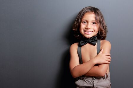 suspender: portrait of cute little boy smiling with arm crossed on dark grey background