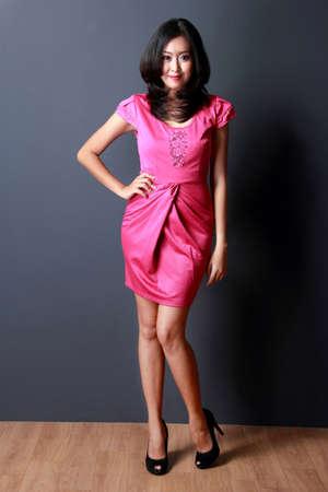 tacones negros: joven y bella mujer posando con un vestido mini rosa Foto de archivo