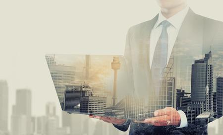 ejecutivos: Doble exposici�n de la ciudad y hombre de negocios usando la computadora port�til Foto de archivo