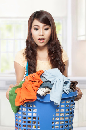woman doing a housework holding laundry photo