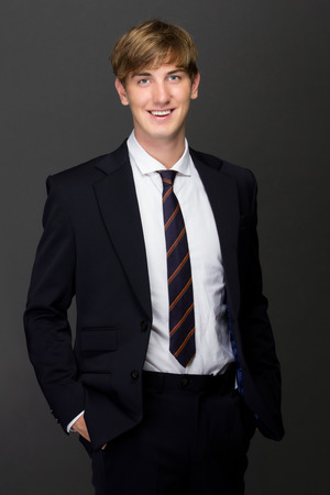 neck tie: a potrait of a smiling young man in black suit with a neck tie